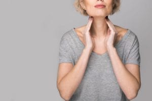 woman thryoid hands touching neck